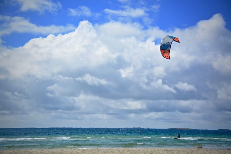 People paragliding on beach against sky
