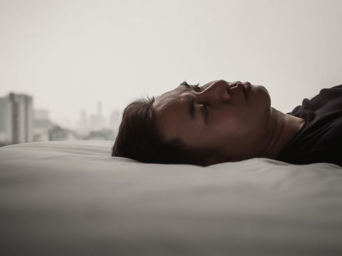 Asian man feels sad alone on bed with city background. stay home, depression and loneliness concept.