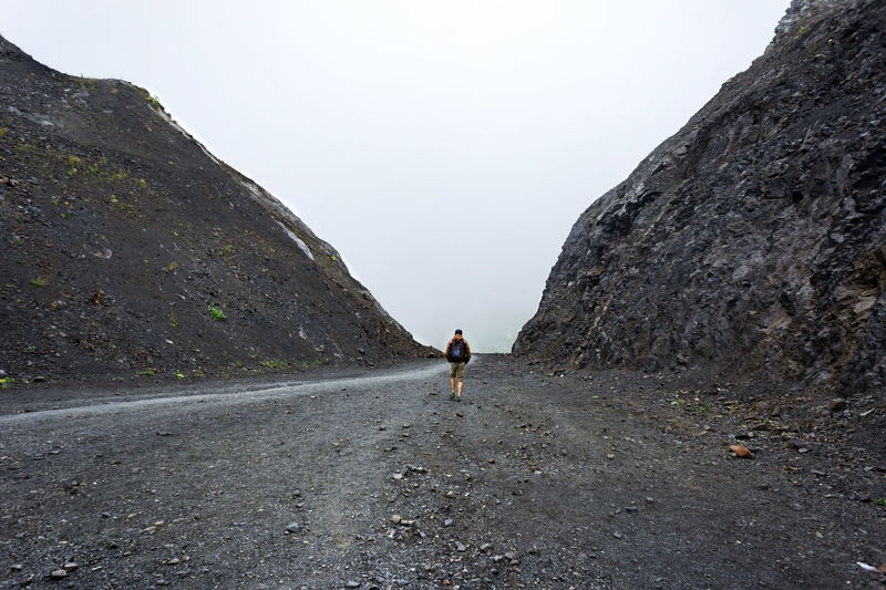 Young man from the back with backpack walking along a path between two rocks. mountain travel alone
