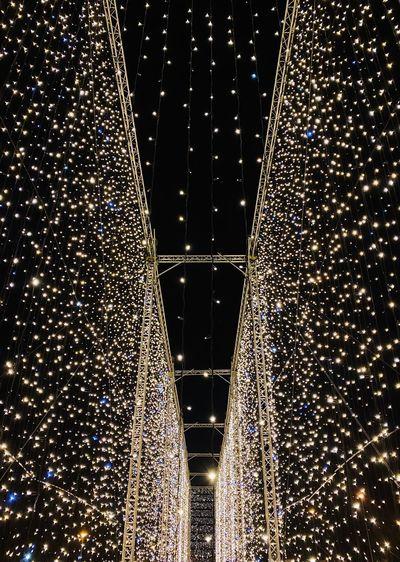 Low angle view of illuminated christmas lights at night
