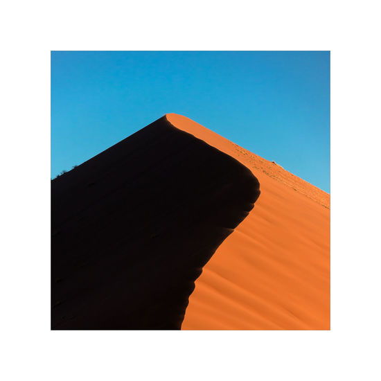 Low angle view of orange structure against blue sky