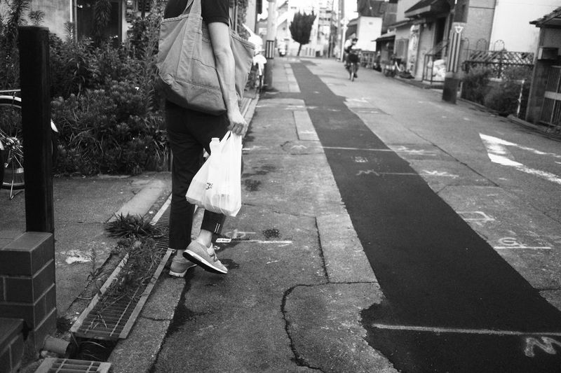 Low section of woman holding shopping bag on street amidst buildings