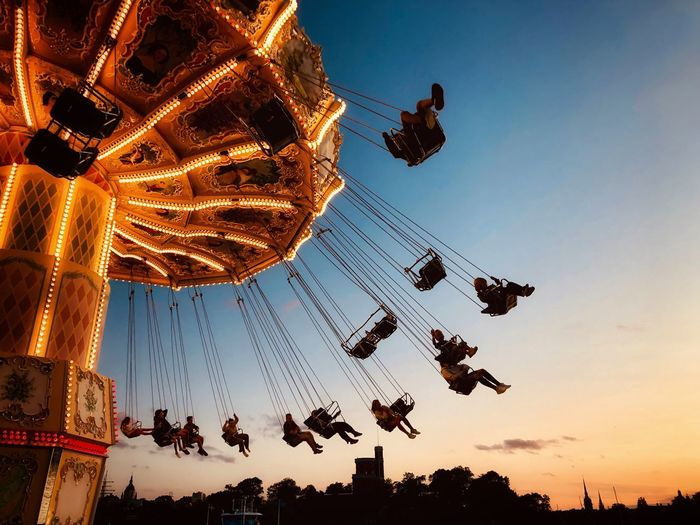People on chain swing ride against sky during sunset