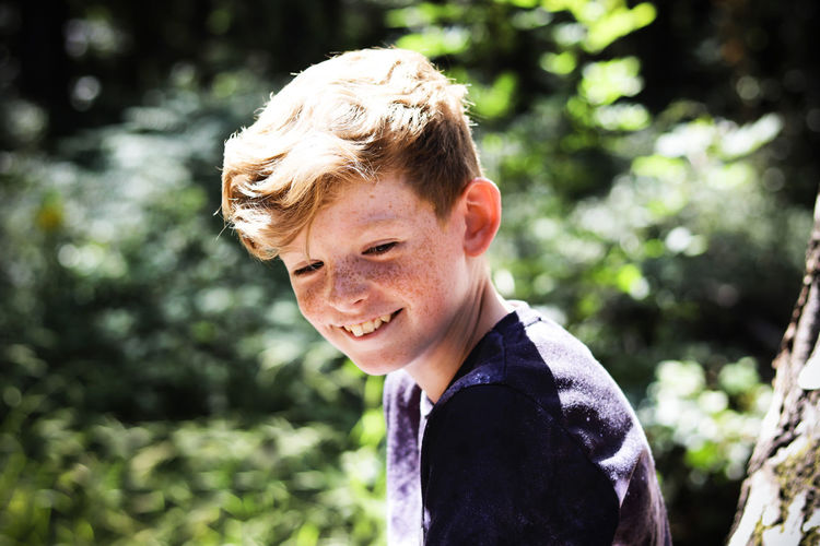 Portrait of boy laughing in the woods. Nature Real Trees Young Youth Boy Boys Child Childhood Emotion Happiness Headshot Innocence Lifestyles Looking At Camera Males  Men Nature One Person Outdoors Portrait Real People Smiling Woods