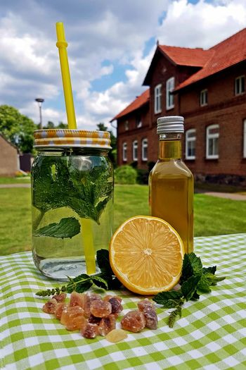 Close-up of fresh lemonade with herbs on table in back yard