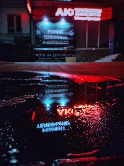 Illuminated city street during rainy season at night