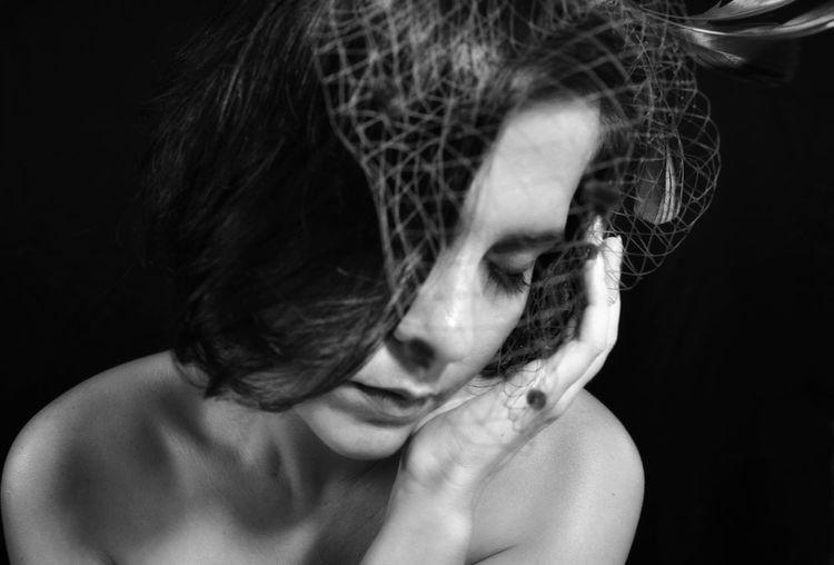 Close-up sad woman against black background