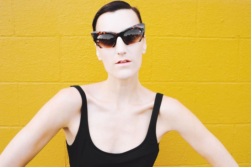 Portrait of young woman wearing sunglasses standing against yellow wall