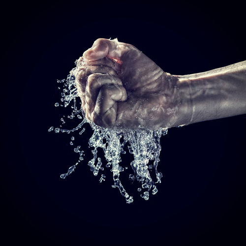 Close-up of wet human hand clenching fist against black background