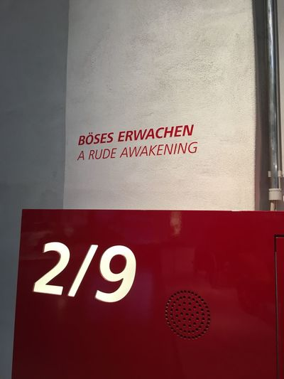 Böses Erwachen 2/9 2/9 Böses Erwachen Rude Awakening Capital Letter Guidance Indoors  Information Information Sign Message No People Number Red Sign Text Wall Western Script White On Red