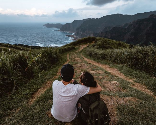 Rear View Of Couple On Mountain Looking At Sea