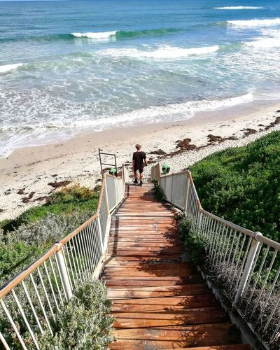 High angle view of man standing on steps leading towards beach
