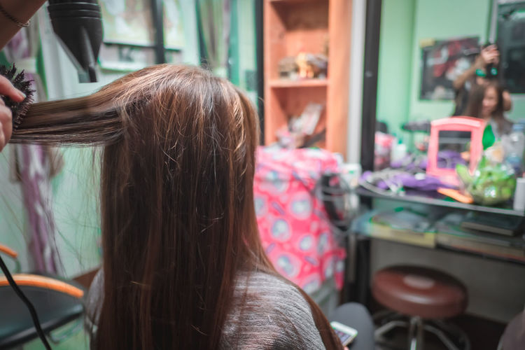 Rear view of woman sitting at barber shop