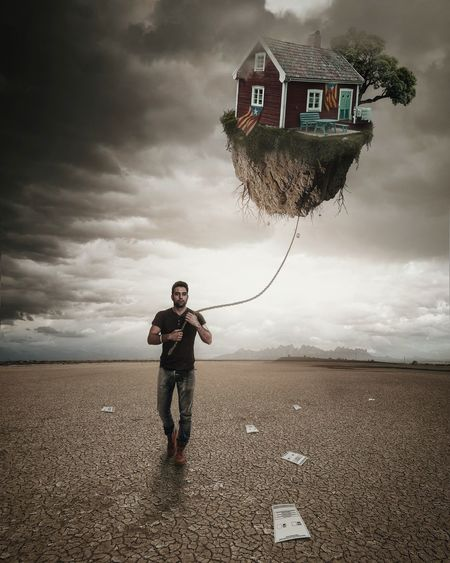 Digital Composite Image Of Young Man Holding House With Rope On Field Against Cloudy Sky