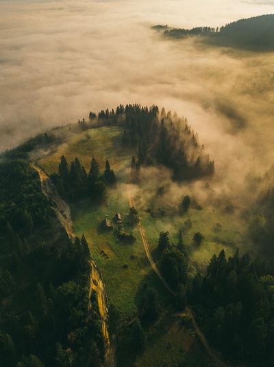 Fantastic sunrise on carpathian mountains. fog spreads on the valley of village, ukraine,