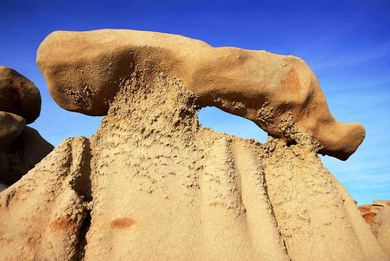 rock formation, nature, rock - object, low angle view, outdoors, physical geography, sunlight, beauty in nature, no people, travel destinations, day, arid climate, clear sky, desert, rock hoodoo, sky