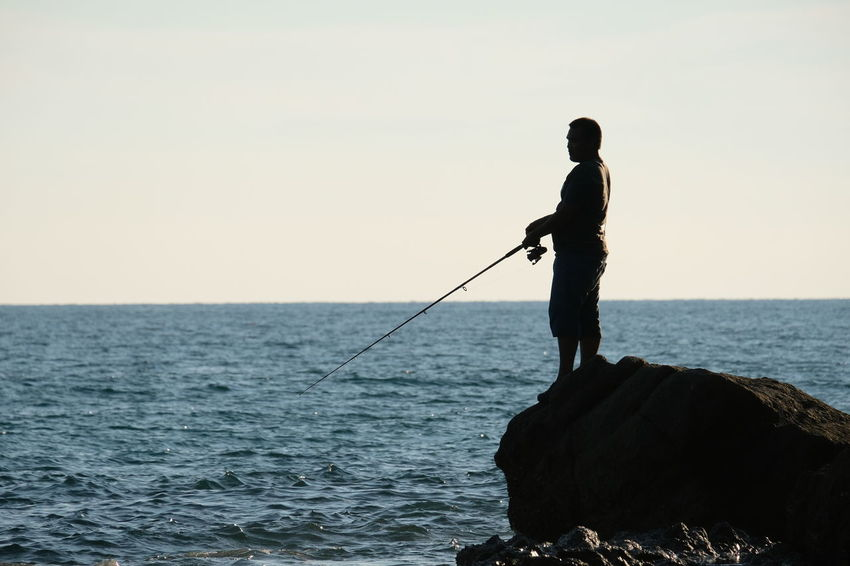 Activity Fishing Horizon Horizon Over Water Leisure Activity Men Nature One Person Outdoors Real People Rock Rock - Object Scenics - Nature Sea Silhouette Sky Solid Standing Water