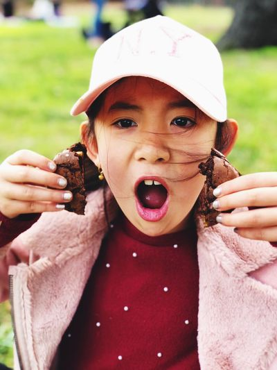 Close-up portrait of shocked girl holding cookies