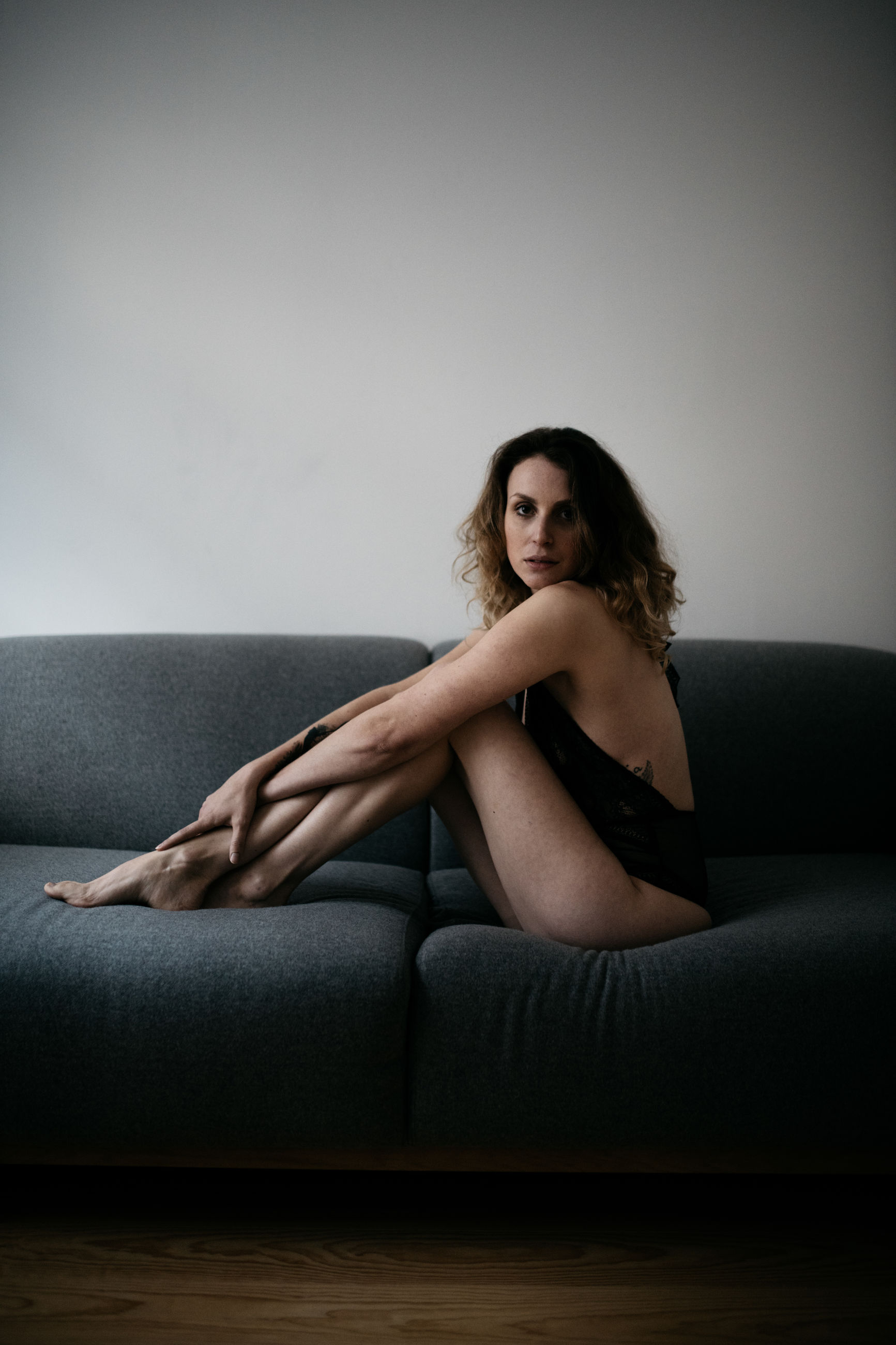 sitting, sofa, one person, indoors, looking at camera, portrait, furniture, lifestyles, full length, hairstyle, beauty, young adult, hair, beautiful woman, long hair, leisure activity, women, real people, contemplation
