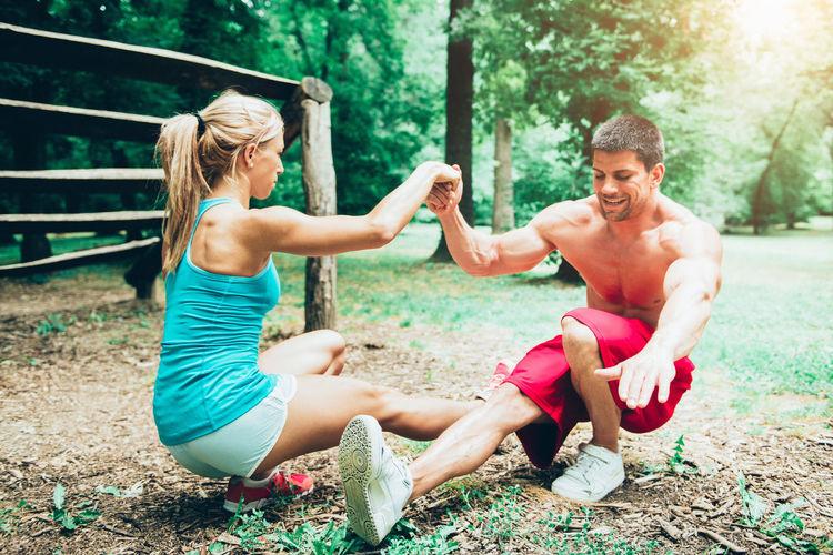 Full Length Of Couple Exercising On Field
