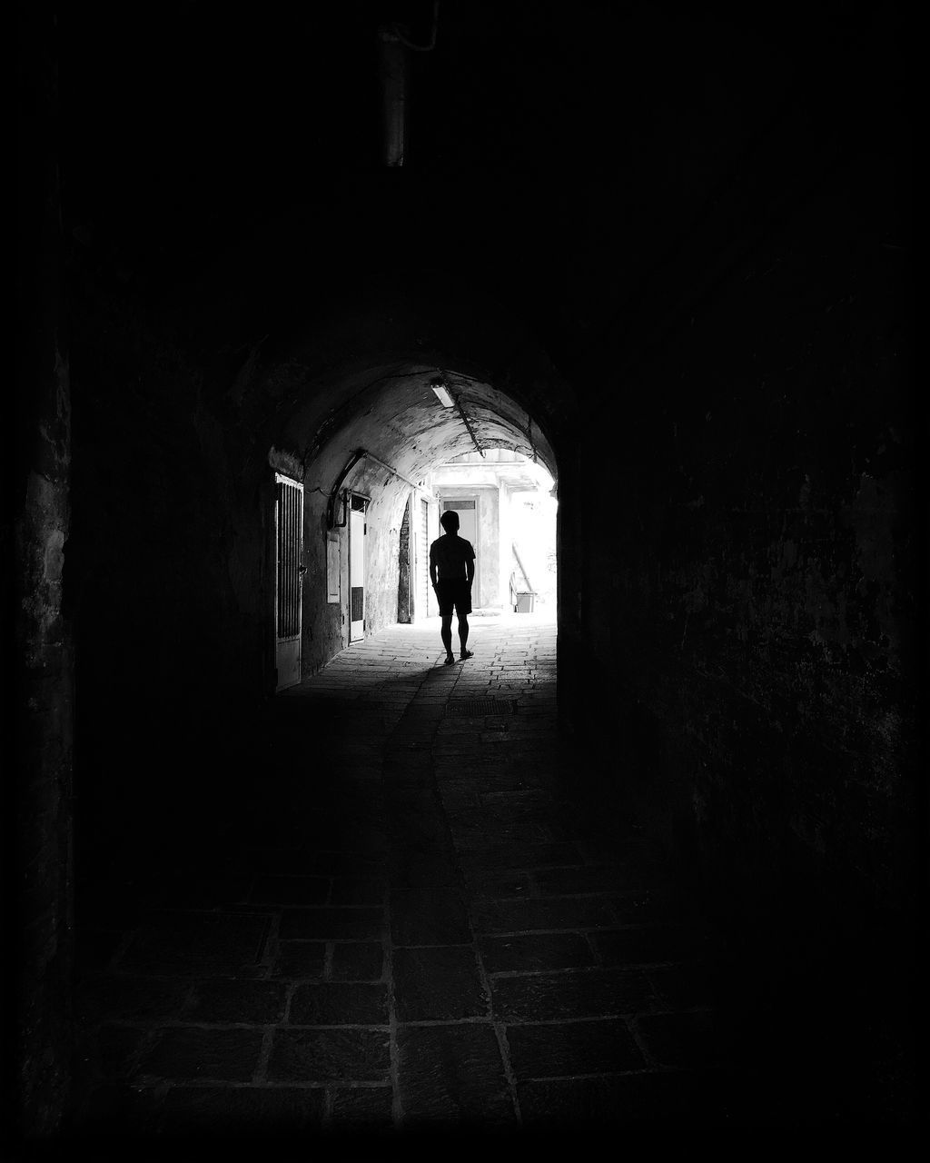architecture, arch, built structure, the way forward, one person, direction, tunnel, full length, indoors, real people, building, lifestyles, walking, men, light at the end of the tunnel, silhouette, day, leisure activity, rear view, dark, arched