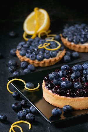 Lemon Tart and tartlets with fresh and cooked blueberries, served on black square plate with lemon and lemon zest over black background. Berries Black Background Desserts Lemon Tarte Shortbread Berry Tartlet Blackberry Blueberry Blueberry Tart Close-up Dessert Food Food And Drink Lemon Zest Pastry Ready-to-eat Shortbread Tartlet Sweet Sweet Food Tart - Dessert Tartlet