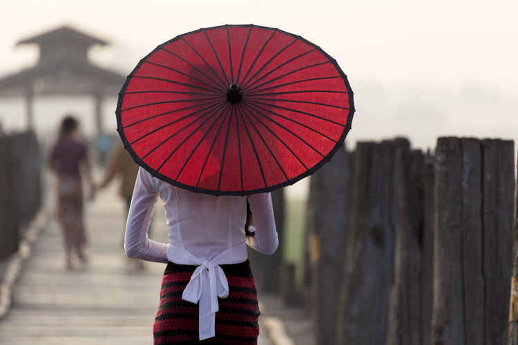 Rear view of woman walking with red umbrella on u bein bridge