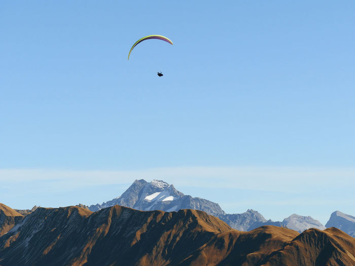 Person paragliding against clear sky