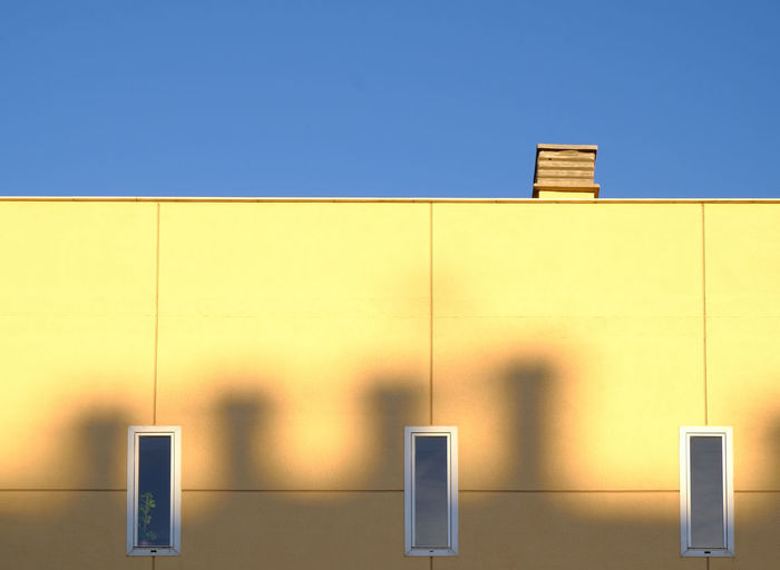 Architecture Blue Building Exterior Built Structure Chimney City Clear Sky Close-up Day Horizontal Symmetry Lines And Patterns Minimalism Paint The Town Yellow Modern Architecture No People Outdoors Shadows & Lights Sky Sunny Day Sunshine Symmetrical Three Windows Torremolinos Yellow Wall The Architect - 2017 EyeEm Awards