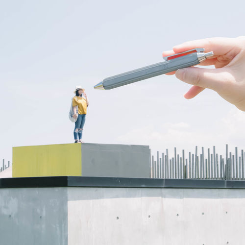 Low angle view of woman holding umbrella standing against building