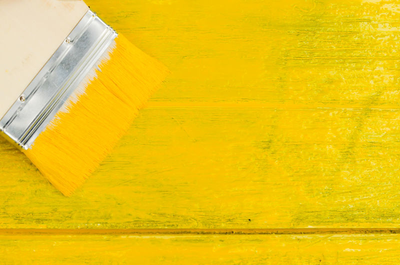 Close-Up Of Paintbrush On Yellow Table