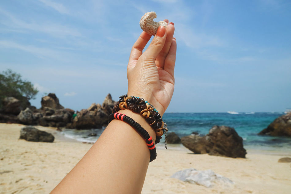 Bohemian Beach Beach Accessories Body Part Bracelet Coral Day Finger Focus On Foreground Hand Holding Horizon Over Water Human Body Part Human Hand Land Leisure Activity Lifestyles Nail Nature One Person Rock Sea Sky Solid Water