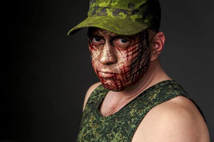 Portrait of soldier with camouflage make-up against black background