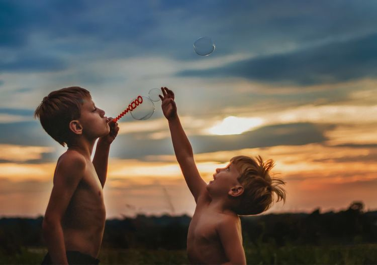 Shirtless friends playing with bubbles against sky during sunset