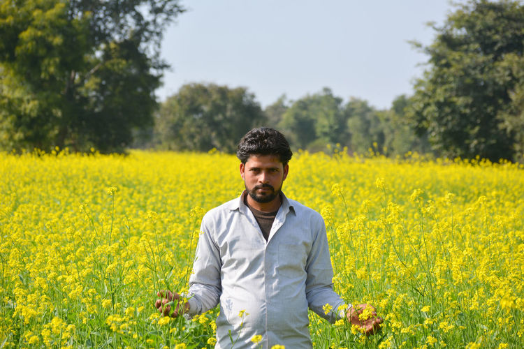 Young indian farmer at black mustard field