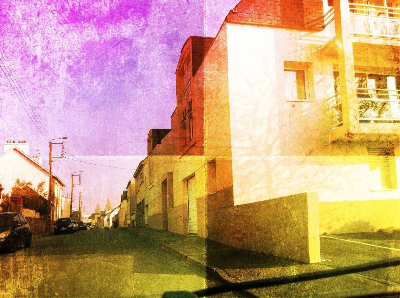 Road by buildings against sky