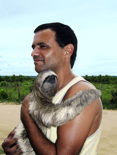 Man with sloth against sky