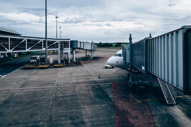 Airplane on airport runway against sky