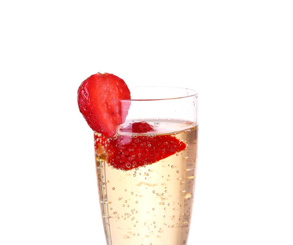 Close-up of strawberry over glass against white background