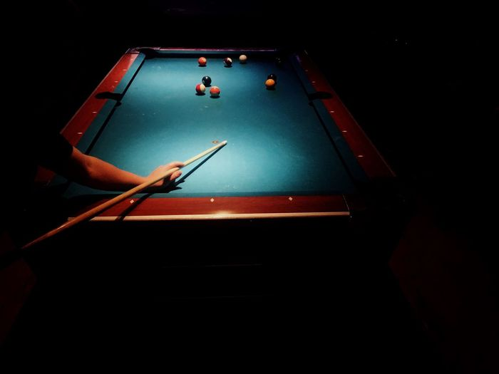 Cropped image of man playing pool in dark