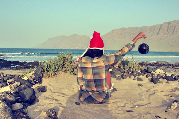 Rear view of woman in santa hat holding bauble while sitting on sand at beach