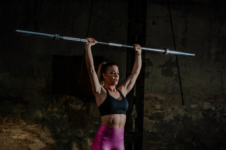 Woman with arms raised standing against the wall