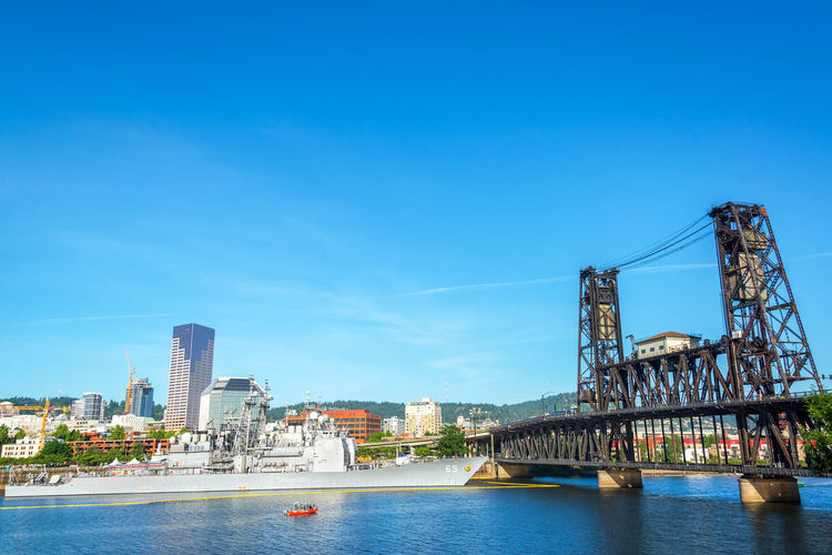 PORTLAND, OR - JUNE 7: View of the Portland, Oregon waterfront with a Navy ship and the Steel Bridge visible on June 7, 2015 during the Rose Festival Blue Boat Coast Guard Downtown Fleet Week Navy Oregon Portland River Rose Festival Royal Canadian Navy Ship Sky Steel Bridge Tom Mccall Waterfront Park US Navy USA Warship Waterfront Willamette Willamette River