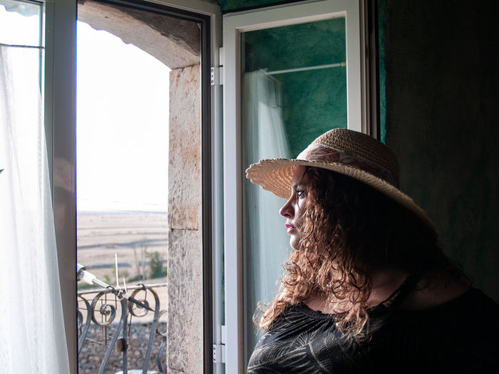 Woman Wearing Hat While Looking Through Window At Home