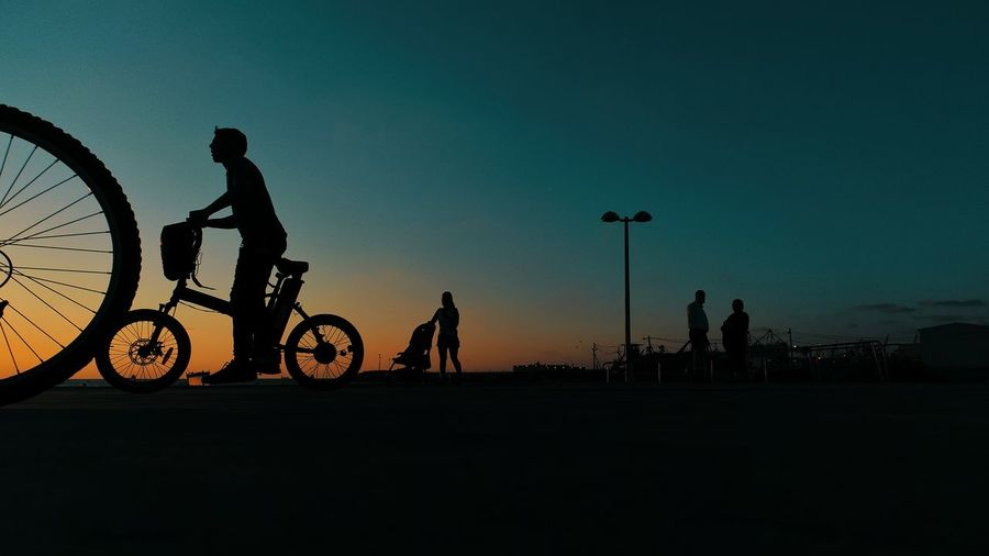 Silhouette man riding bicycle on road against sky
