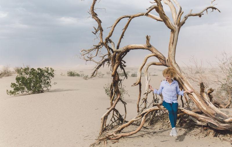 Mid adult woman sitting on tree at desert against sky