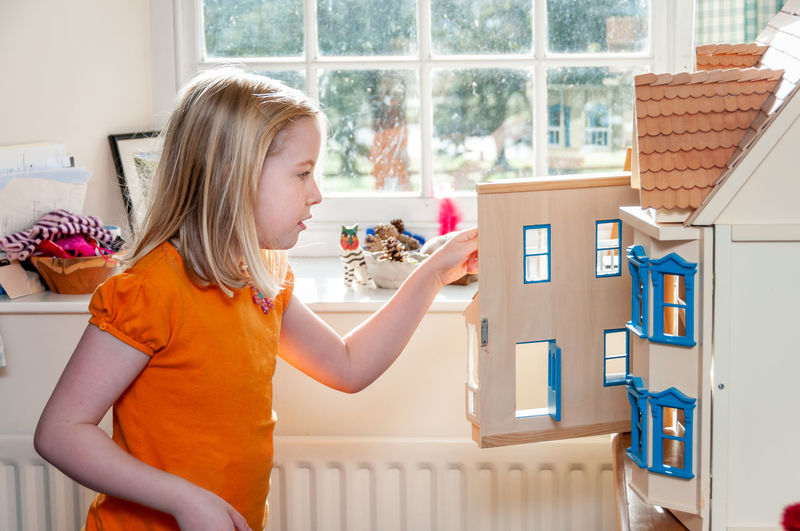 Side view of girl holding window at home