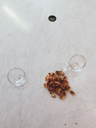 High Angle View Of Pistachio Nuts And Glasses On Table