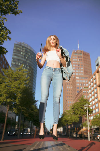 Woman levitating against buildings