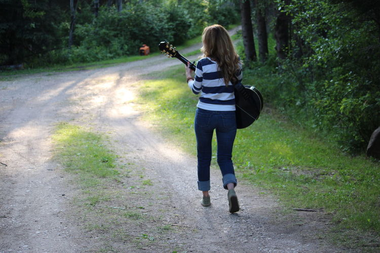 Rear view of young woman playing guitar while walking on footpath